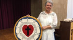 Cindy Swanson holding cross stitch version of Luther's Rose