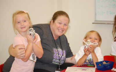 children making crafts with volunteer during VBS