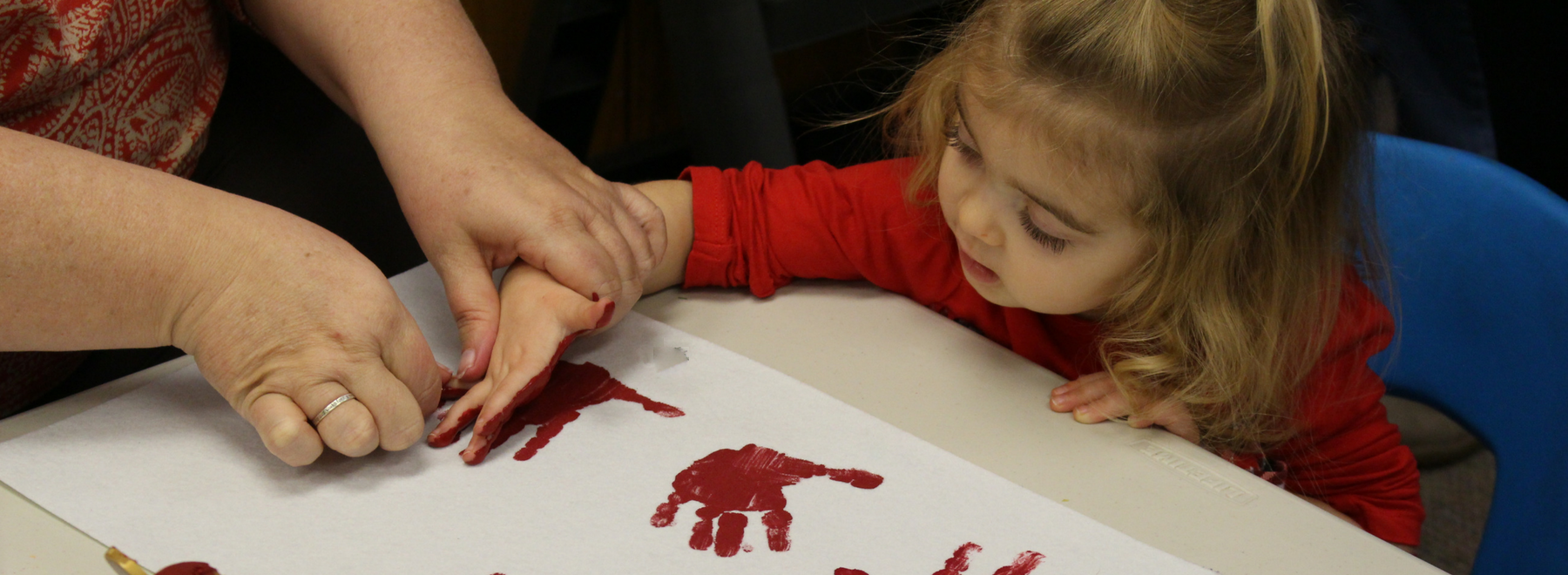 child in children's ministry doing painted hand prints